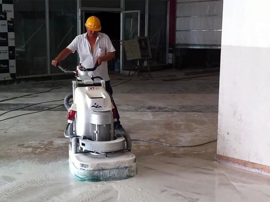 Một người đang điều khiển thiết bị mài nền nhà xưởng để chuẩn bị thi công sơn epoxy
